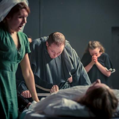 Niamh McAllister (Grusha), Kyle Hixon (Monk) and ensemble in The Caucasian Chalk Circle. Photo by Keith Dixon.